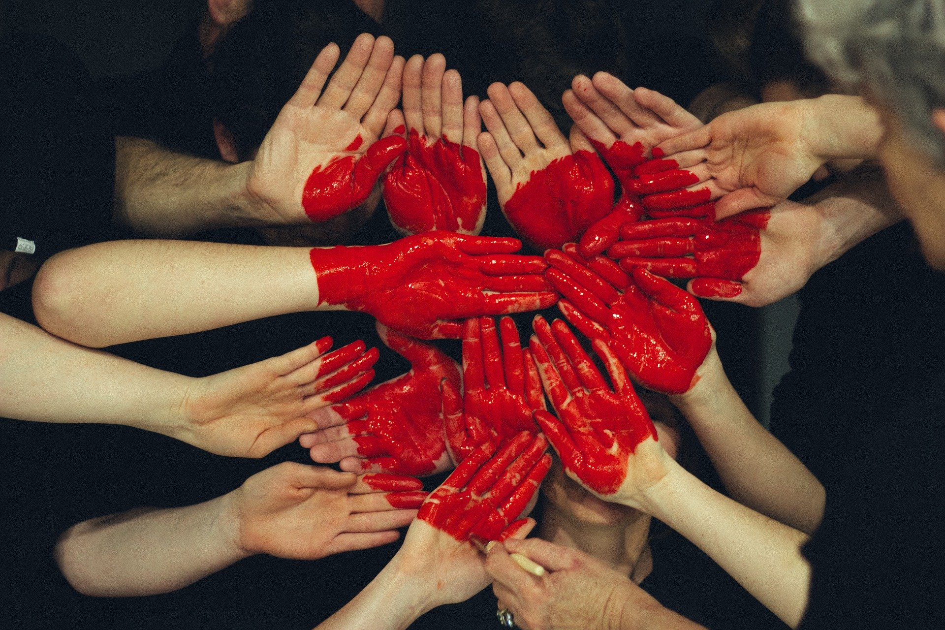 primer plano de las palmas de las manos de muchos adultos, que en conjunto tienen pintado un corazón en rojo