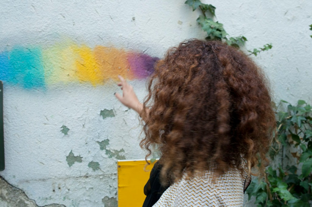 foto de criando247.com  Mujer de espaldas señalando un  arcoiris pintado sobre una pared blanca