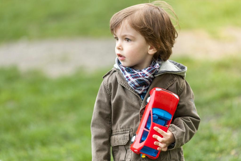 niño pequeño mirando de lado con cara de sorpresa, con un coche de juguete rojo en su mano. está en un parque