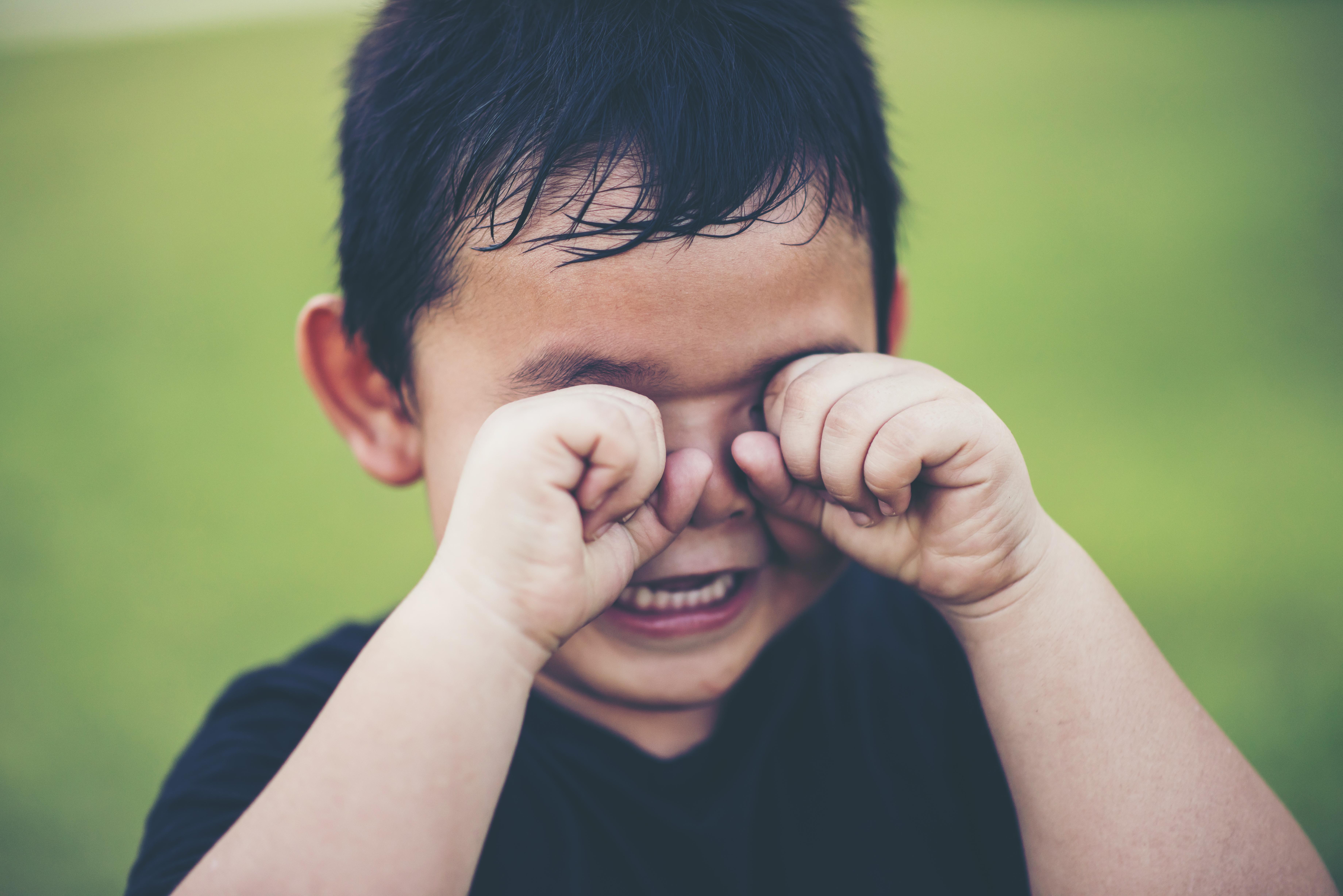 Niño pequeño llorando con los puños en los ojos