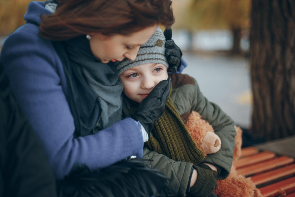 madre e hijo sentados en un banco de un parque. Ella lo abrazo y tiene sus manos, con guantes, sosteniendo la carita del niño con signo de contención . el niño sonríe mientras abraza un oso de peluche
