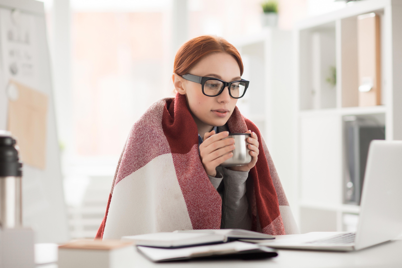 Mujer joven con gafas, sentada frente a un escritorio mirando concentrada a la pantalla de un portatil mientras sostiene una taza metálica entre ambas manos. Tiene una manta cubriendo sus hombros.