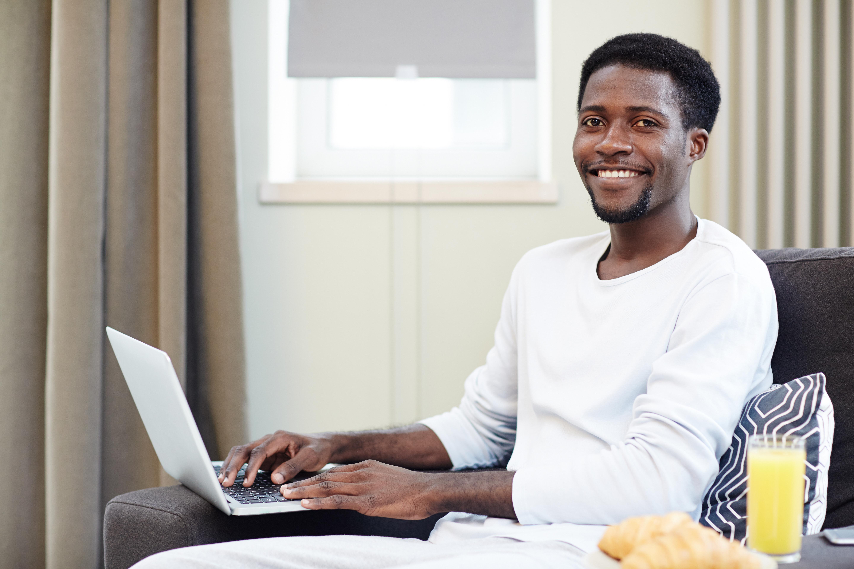 Hombre joven sonríe a cámara mientras posa sus manos sobre el teclado de un portatil apoyado en el sofá. A su lado un zumo de naranja y unos croissants.