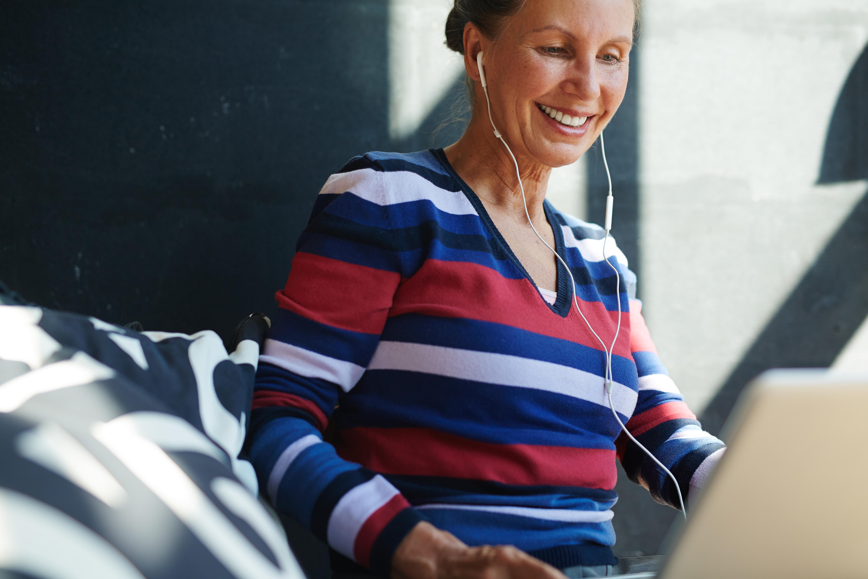 Mujer madura, sentada en el sofá con unos cascos puestos sonríe mientras mira a la pantalla de su portatil haciendo terapia online