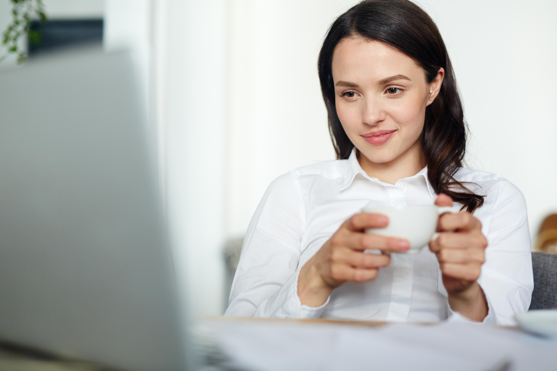 Mujer sosteniendo una taza blanca con ambas manos, sentada, mirando la pantalla de un portatil mientras esboza una sonrisa