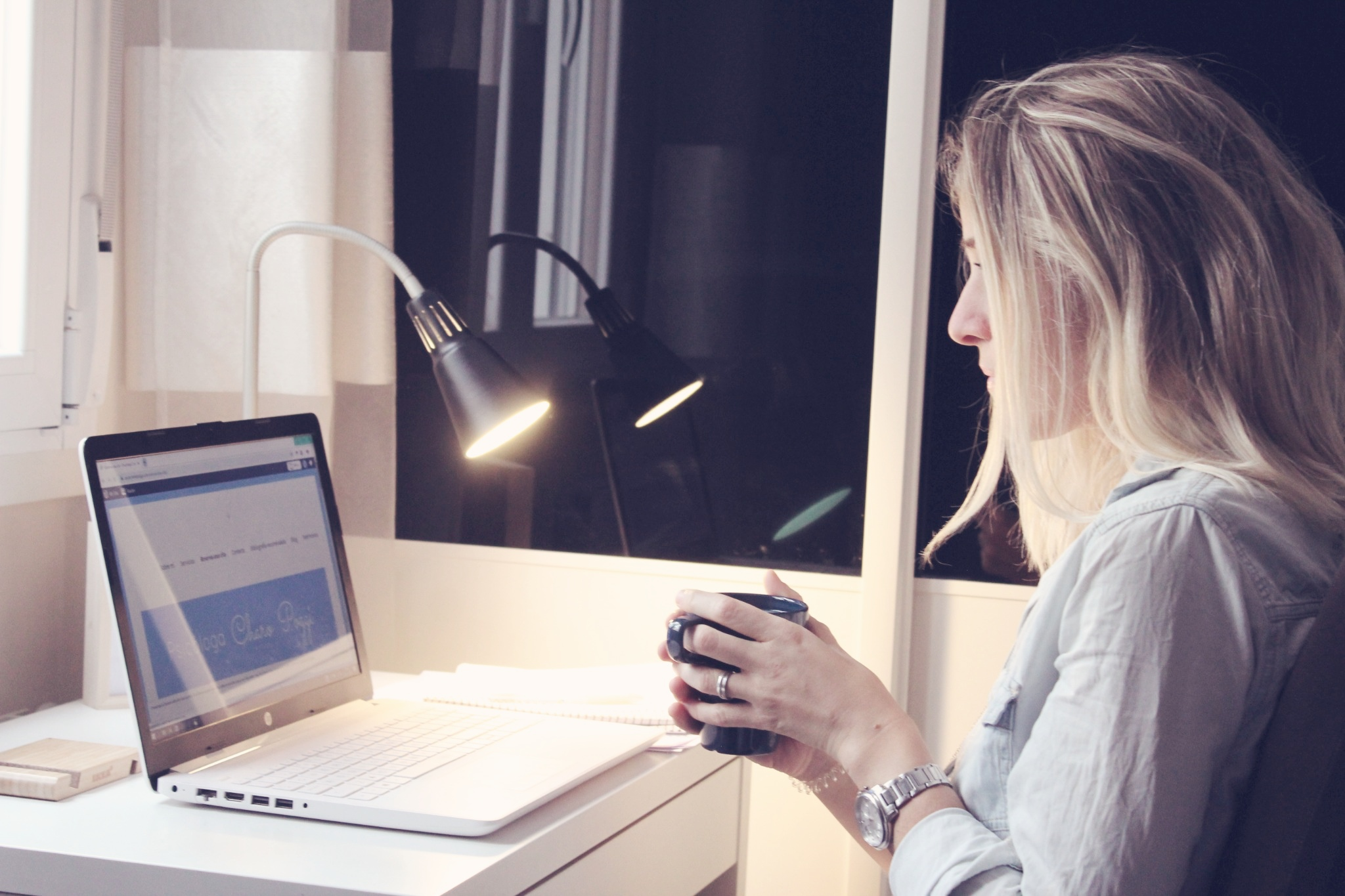 La Psicóloga Charo Poggi, mujer joven rubia, sentada mientras sostiene una taza con ambas manos, mira hacia la pantalla de su portatil donde se ve la web de psicocharopoggi.com