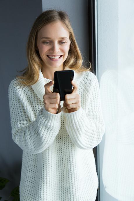 Mujer joven de pie junto a una ventana, sonríe mientras mira la pantalla de su móvil