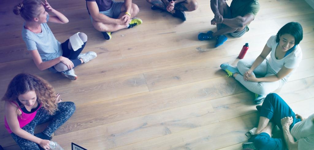 grupo de personas sentadas en el suelo en círculo