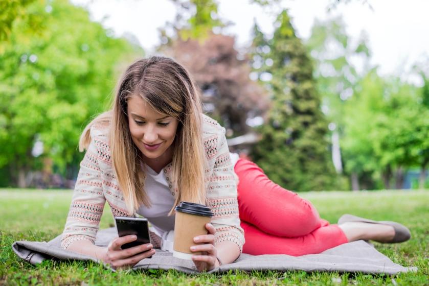 Mujer tumbada sobre una manta sobre el cesped de un parque, sonríe mientras mira a su movil y sostiene un vaso de café descartable.