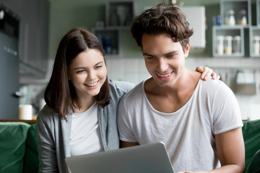 Pareja de hombre y mujer sentados en el sofá sonriendo mientras miran la pantalla de su ordenador
