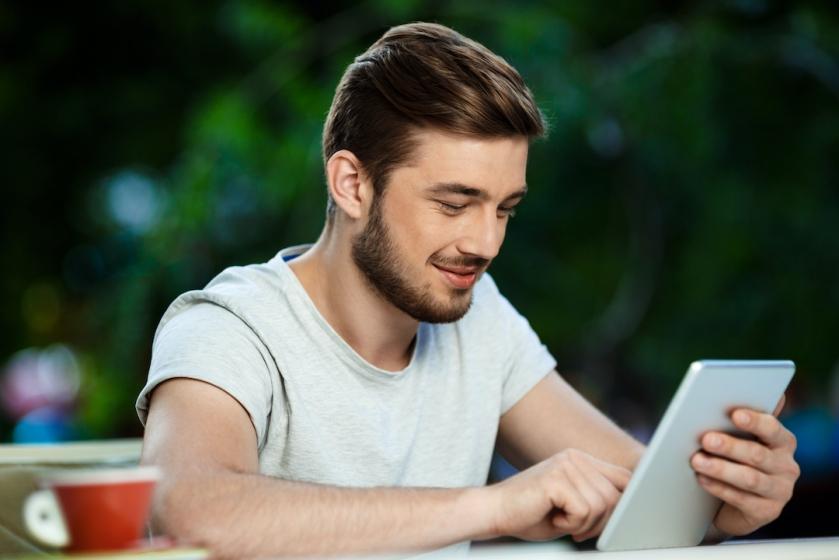 Hombre joven sonríe mientras mira a su tablet