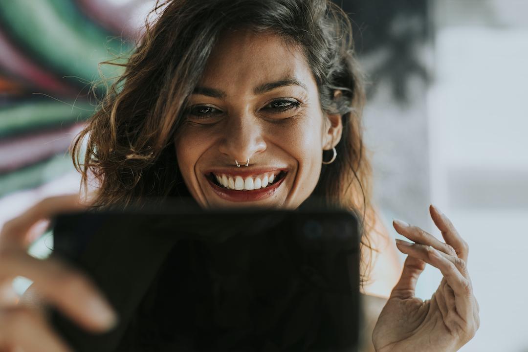 mujer joven sonríe mientras mira la pantalla de su tablet