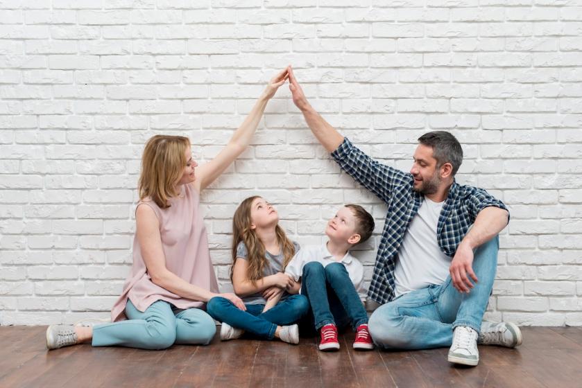 familia de padre y madre uniendo sus manos por encima de sus hijo e hija, todos sentados en el suelo y sonriendo