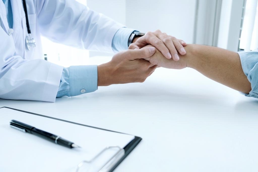 manos de doctor sostienen manos paciente